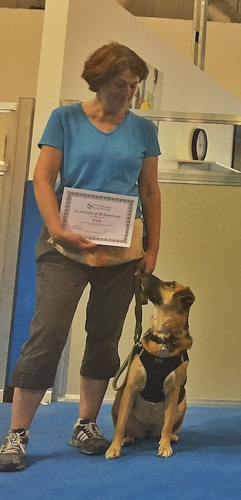 Ziva sits looking up at Sue, who is holding her certificate